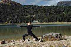 Γιόγκα άσκησης ατόμων κοντά στη μαύρη λίμνη φθινοπώρου, Durmitor Nationa στοκ φωτογραφία