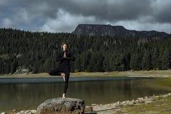 Γιόγκα άσκησης ατόμων κοντά στη μαύρη λίμνη φθινοπώρου, Durmitor Nationa στοκ εικόνα