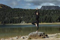 Γιόγκα άσκησης ατόμων κοντά στη μαύρη λίμνη φθινοπώρου, Durmitor Nationa στοκ φωτογραφία με δικαίωμα ελεύθερης χρήσης