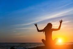 Γιόγκα άσκησης γυναικών κατά τη διάρκεια ενός καταπληκτικού ηλιοβασιλέματος στη θέση Lotus στην παραλία θάλασσας Στοκ φωτογραφία με δικαίωμα ελεύθερης χρήσης