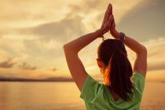 Γιόγκα άσκησης γυναικών με την επίκληση της χειρονομίας μπροστά από τ στοκ φωτογραφία