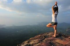 Γιόγκα άσκησης γυναικών στη μέγιστη άκρη απότομων βράχων βουνών Στοκ Εικόνα