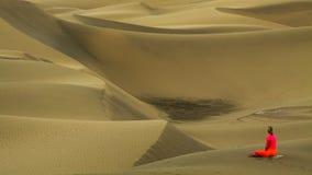 Γιόγκα άσκησης γυναικών στους αμμόλοφους άμμου στοκ εικόνα