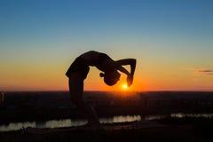 Γιόγκα άσκησης γυναικών στο ηλιοβασίλεμα - η πλάτη πτώσης, ρόδα θέτει Στοκ Εικόνες