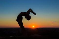 Γιόγκα άσκησης γυναικών στο ηλιοβασίλεμα - η πλάτη πτώσης, ρόδα θέτει Στοκ Φωτογραφία
