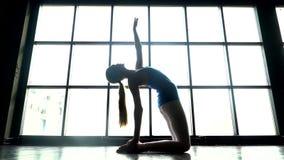 Γιόγκα άσκησης γυναικών στο κλίμα παραθύρων μια ηλιόλουστη ημέρα Καυκάσιο νέο κορίτσι που κάνει την άσκηση γιόγκας κορίτσι φίλαθλ φιλμ μικρού μήκους