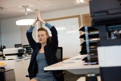 Γιόγκα άσκησης επιχειρηματιών καθμένος στην καρέκλα από το γραφείο στοκ εικόνα