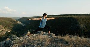 Γιόγκα άσκησης νεαρών άνδρων στο βράχο στο ηλιοβασίλεμα φιλμ μικρού μήκους