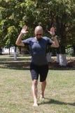 Γιόγκα κατάρτισης νεαρών άνδρων υπαίθρια Ο φίλαθλος τύπος κάνει την τεντώνοντας άσκηση σε ένα μπλε χαλί γιόγκας, στο χώρο αθλήσεω στοκ εικόνες