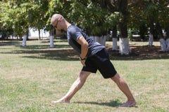 Γιόγκα κατάρτισης νεαρών άνδρων υπαίθρια Ο φίλαθλος τύπος κάνει την τεντώνοντας άσκηση σε ένα μπλε χαλί γιόγκας, στο χώρο αθλήσεω στοκ εικόνα