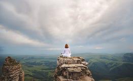 Γιόγκα πρακτικών γυναικών και meditates στα βουνά Στοκ εικόνα με δικαίωμα ελεύθερης χρήσης