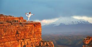 Γιόγκα πρακτικών γυναικών και meditates στα βουνά Στοκ Εικόνες