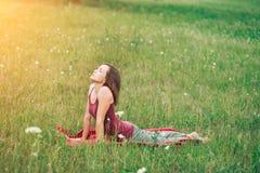 Γιόγκα στη φύση, μια όμορφη γυναίκα που κάνει τη γυμναστική, ασκήσεις στο λιβάδι Στοκ εικόνες με δικαίωμα ελεύθερης χρήσης