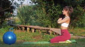 Γιόγκα στη φύση, νέο ελκυστικό κορίτσι γιόγκη που και που κάνει οι ασκήσεις γιόγκας στην πράσινη χλόη μεταξύ των δέντρων φιλμ μικρού μήκους