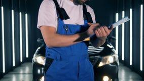 Γκαράζ και ένας μηχανικός που παίρνει τις σημειώσεις μετά από την εξέταση του αυτοκινήτου απόθεμα βίντεο