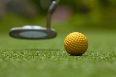 Γκολφ κλαμπ και κίτρινη σφαίρα στην τεχνητή χλόη Στοκ Φωτογραφία
