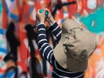 Γκράφιτι ζωγραφικής ψεκασμού χρωμάτων εκμετάλλευσης αγοριών Στοκ εικόνες με δικαίωμα ελεύθερης χρήσης