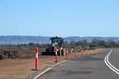 Γκρέιντερ που καθαρίζει το θάμνο κατά μήκος της πλευράς της εθνικής οδού στοκ εικόνες με δικαίωμα ελεύθερης χρήσης