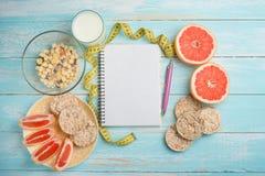 Γκρέιπφρουτ, ψωμί muesli, και ένα καθαρό σημειωματάριο για το γράψιμο Η έννοια της διατροφής στοκ φωτογραφία