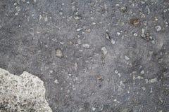 Γκρίζα άσφαλτος με το λεκέ χρωμάτων και τη σύσταση πετρών Τοίχος τσιμέντου με τους λεκέδες και την κινηματογράφηση σε πρώτο πλάνο Στοκ Φωτογραφίες