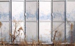 Γκρίζα διπλώνοντας πόρτα μετάλλων σε μια εγκαταλειμμένη αποθήκη εμπορευμάτων Στοκ Φωτογραφία