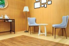 Γκρίζα καρέκλα μαξιλαριών και άσπρη ξύλινη καρέκλα με το λαμπτήρα στο ξύλινο λι Στοκ φωτογραφία με δικαίωμα ελεύθερης χρήσης
