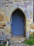 Γκρίζα ξύλινη πόρτα κάτω από την πέτρινη αψίδα στοκ εικόνα