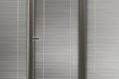 Γκρίζα οριζόντια γρίλληα παραθύρου στο παράθυρο Στοκ Φωτογραφία