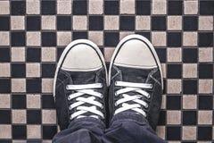 Γκρίζα πάνινα παπούτσια στο ελεγμένο πεζοδρόμιο σχεδίων, τοπ άποψη Στοκ Εικόνες