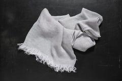 Γκρίζα πετσέτα χεριών με τα άσπρα περιθώρια στη σκοτεινή επιφάνεια Στοκ Εικόνες