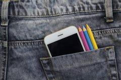 Γκρίζα τζιν με τα άσπρα μολύβια smartphone και χρώματος στη μαύρη τσέπη Στοκ Φωτογραφίες