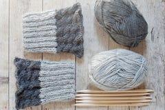 Γκρίζα legwarmers μαλλιού, πλέκοντας βελόνες και νήμα Στοκ Εικόνα