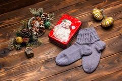 Γκρίζες μάλλινες πλεκτές κάλτσες, διακοσμήσεις Χριστουγέννων και ένα κιβώτιο μετάλλων με την εικόνα Άγιου Βασίλη σε ένα ξύλινο υπ στοκ φωτογραφία