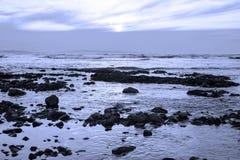 Γκρίζοι βράχοι στη δύσκολη μπλε παραλία Στοκ Εικόνες