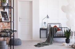 Γκρίζοι λαμπτήρας, ρολόι και βιβλία στο μαύρο nightstand δίπλα στο comfy κρεβάτι με την γκρίζα κλινοστρωμνή και τα πορφυρά και άσ στοκ φωτογραφία