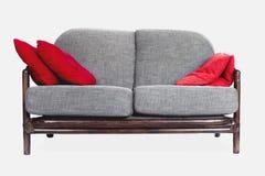 Γκρίζος καναπές στο άσπρο υπόβαθρο, κόκκινα μαξιλάρια στοκ εικόνες