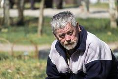 Γκρίζος-μαλλιαρή γενειοφόρος παλαιά συνεδρίαση ατόμων σε έναν πάγκο και τα βλέμματα στοκ φωτογραφία με δικαίωμα ελεύθερης χρήσης
