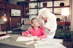 Γκρίζος-μαλλιαρή γιαγιά σχετικά με τη μύτη του καλού χαριτωμένου κοριτσιού της στοκ εικόνα με δικαίωμα ελεύθερης χρήσης