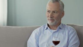 Γκρίζος-μαλλιαρή συνεδρίαση ατόμων στο ποτήρι καναπέδων και εκμετάλλευσης του κρασιού, που απολαμβάνει τη μυρωδιά του απόθεμα βίντεο