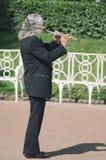Γκρίζος-μαλλιαρός φλαουτίστας οδών που παίζει το φλάουτο στοκ εικόνες