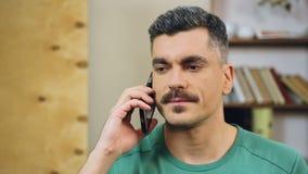 Γκρίζος-μαλλιαρό άτομο που μιλά στο κινητό τηλέφωνο στο σπίτι, που κάνει τη συνάντηση με τους φίλους απόθεμα βίντεο