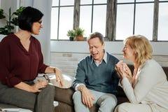 Γκρίζος-μαλλιαρό άτομο που φωνάζει κατά τη διάρκεια της συνόδου ενώ η σύζυγός του που διασχίζει τα δάχτυλά της στοκ φωτογραφία με δικαίωμα ελεύθερης χρήσης