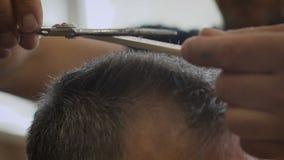 Γκρίζος-μαλλιαρό άτομο σε ένα κατάστημα κουρέων Μοντέρνος πελάτης κουρέων strizhot που χρησιμοποιεί μια χτένα και ένα ψαλίδι Αργή φιλμ μικρού μήκους