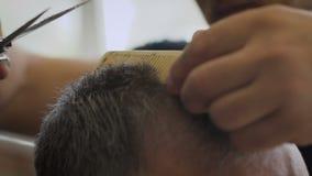 Γκρίζος-μαλλιαρό άτομο σε ένα κατάστημα κουρέων Μοντέρνος πελάτης κουρέων strizhot που χρησιμοποιεί μια χτένα και ένα ψαλίδι Αργή απόθεμα βίντεο