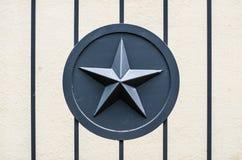 Γκρίζος στρατός αστεριών μετάλλων στρατιωτικός στην πύλη φρακτών μετάλλων στοκ εικόνες