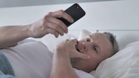 Γκρίζο άτομο τρίχας που αντιδρά στην απώλεια χρησιμοποιώντας Smartphone στο κρεβάτι απόθεμα βίντεο