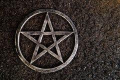 Γκρίζο μέταλλο pentagram στο υπόβαθρο πλακών με τις πτώσεις νερού στοκ εικόνες