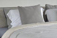 Γκρίζο μαξιλάρι στην άσπρη ρύθμιση στο κρεβάτι με το comfy κάλυμμα στοκ εικόνα