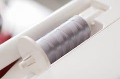 Γκρίζο νήμα σε ρηχό βάθος μηχανών ραψίματος του τομέα (μαλακό focu στοκ φωτογραφία