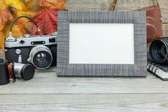 Γκρίζο ξύλινο υπόβαθρο με την κλασική κάμερα, κενό πλαίσιο φωτογραφιών, λ Στοκ Εικόνα